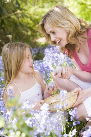 discovering: Mother and daughter on Easter looking for eggs outdoors smiling Stock Photo