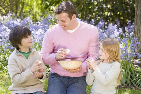 Father and two young children on Easter looking for eggs outdoors smiling photo