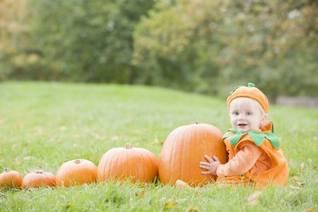 calabazas de halloween: Baby Boy al aire libre en traje de calabaza real con calabazas