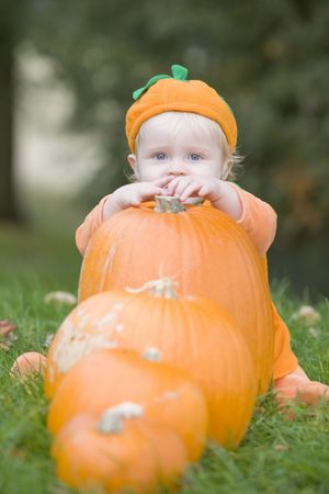 Baby boy outdoors in pumpkin costume with real pumpkins
