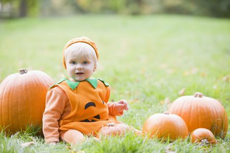 Baby boy outdoors in pumpkin costume with real pumpkins photo