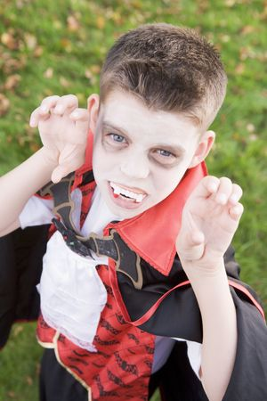 Young boy outdoors wearing vampire costume on Halloween photo
