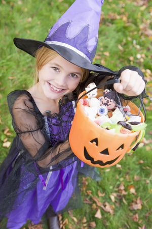 trick or treating: Young girl outdoors in witch costume on Halloween holding candy