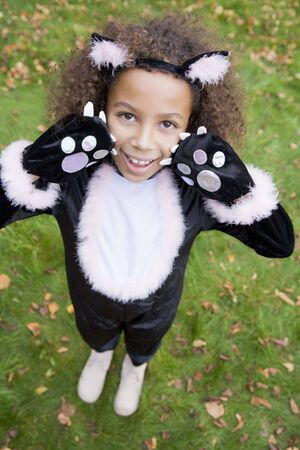 dressing up costume: Young girl outdoors in cat costume on Halloween Stock Photo