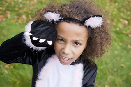 dressing up costume: Young girl outdoors in cat costume on