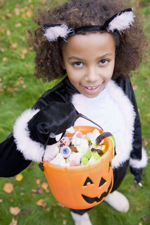 Young girl outdoors in cat costume on Halloween holding candy Stock Photo - 3488339