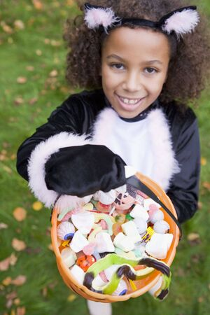 trick or treating: Young girl outdoors in cat costume on Halloween holding candy