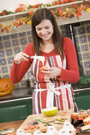 Woman in kitchen making Halloween treats and smiling photo