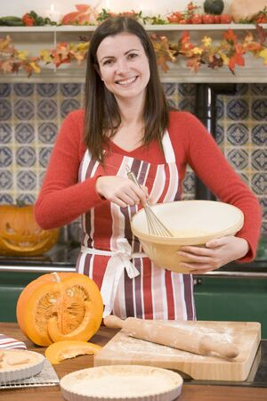 Woman in kitchen making Halloween treats and smiling Stock Photo - 3488346