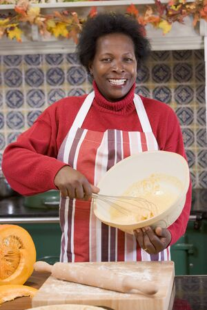 holiday cooking: Woman in kitchen making Halloween treats and smiling
