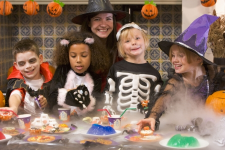 children party: Four young friends and a woman at Halloween eating treats and smiling
