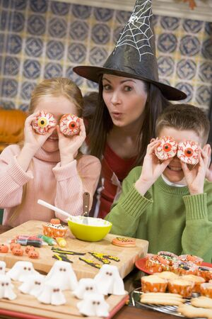dressing up costume: Mother and two children at Halloween playing with treats and smiling