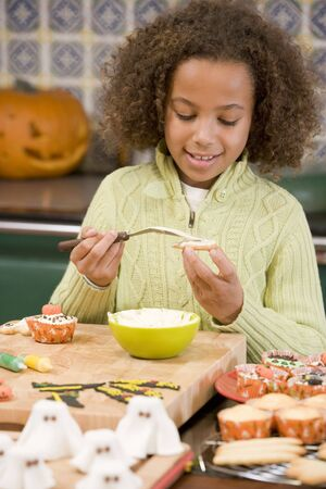 Young girl at Halloween making treats and smiling photo