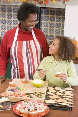 Grandmother and granddaughter making Halloween treats and smiling photo