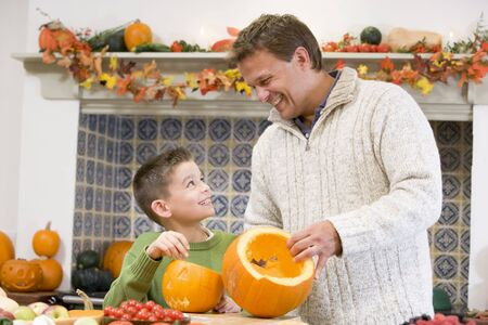 Father and son carving jack o lanterns on Halloween and smiling photo