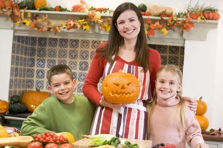 calabazas de halloween: Madre y dos hijos talla jack o linternas en Halloween y sonriente