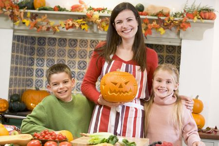 Mother and two children carving jack o lanterns on Halloween and smiling photo