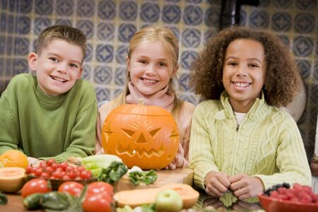 halloween pumpkins: Three young friends on Halloween with jack o lantern and food smiling