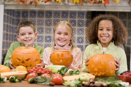pumpkin carving: Three young friends on Halloween with jack o lanterns and food smiling