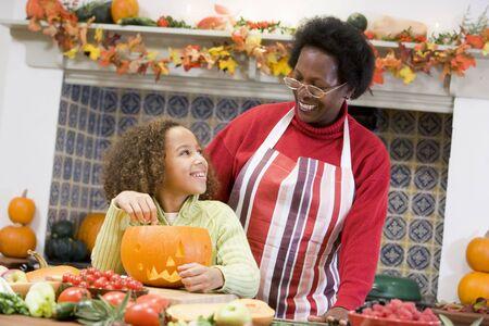 Grandmother and granddaughter making jack o lantern on Halloween smiling photo