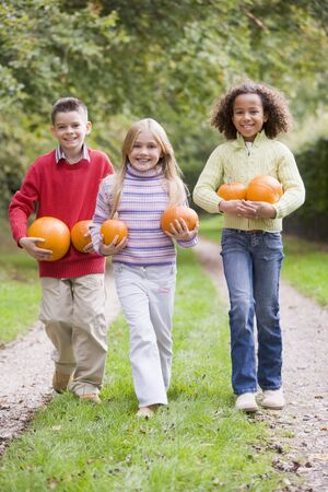 Three young friends walking on path with pumpkins smiling photo