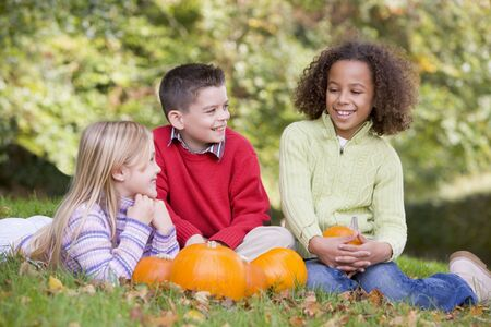 Three young friends sitting on grass with pumpkins smiling photo