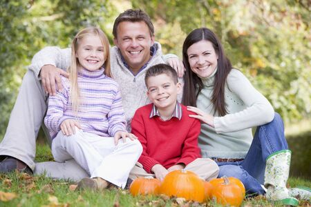 Family sitting on grass with pumpkins smiling photo