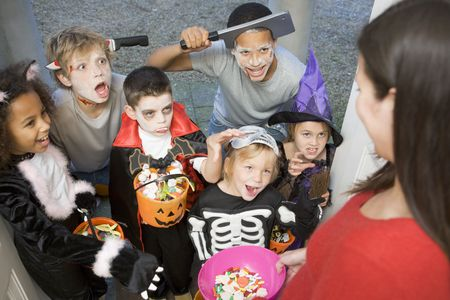 Six children in costumes trick or treating at woman's house Stock Photo
