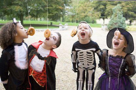 Four young friends on Halloween in costumes eating donuts hanging off strings