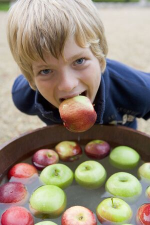 Young boy bobbing for apples photo