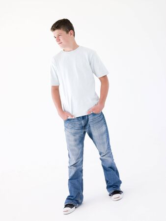 Teenage boy standing with hands in pockets photo