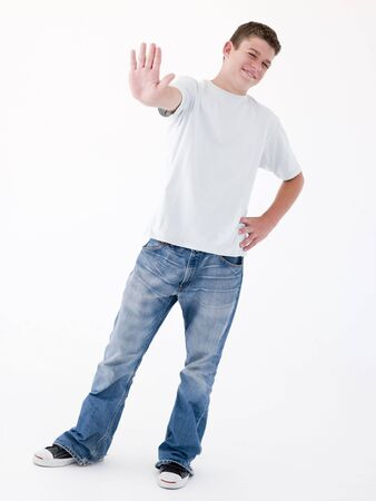 confrontational: Teenage boy standing with hand up
