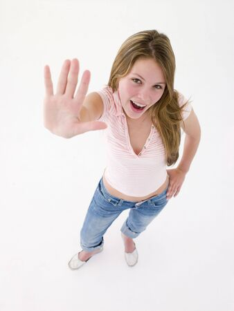 confrontational: Teenage girl with hand up smiling Stock Photo