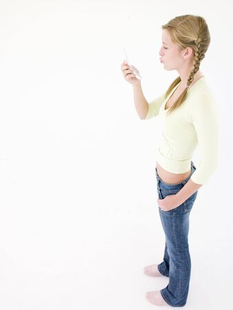 puckering: Teenage girl looking at cellular phone and puckering up Stock Photo
