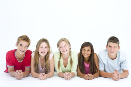 group of teenagers: Five friends lying down in a row smiling