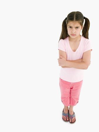 defiance: Young girl with arms crossed angry Stock Photo