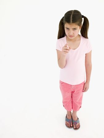 confrontational: Young girl pointing and frowning