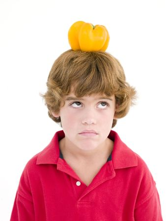 Young boy with yellow pepper on his head frowning photo