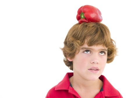 Young boy with red pepper on his head frowning Stock Photo
