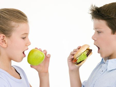 Sister eating apple by brother eating cheeseburger photo