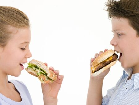 fast eat: Sister eating sandwich by brother eating cheeseburger