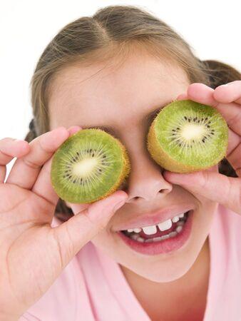 Young girl holding kiwi halves over eyes smiling photo