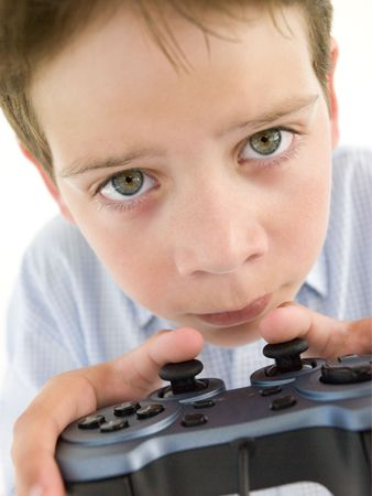 videogame: Young boy using videogame controller and concentrating