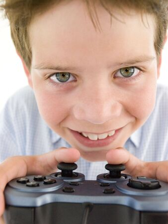 videogame: Young boy using videogame controller smiling
