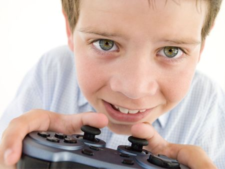 Young boy using videogame controller smiling
