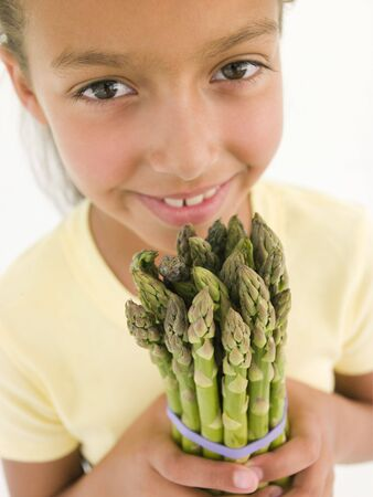 Young girl holding bunch of asparagus and smiling photo