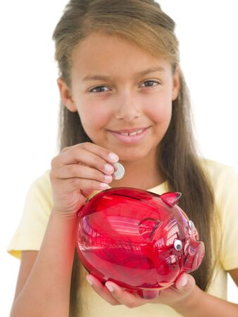 Young girl putting coin into piggy bank smiling photo
