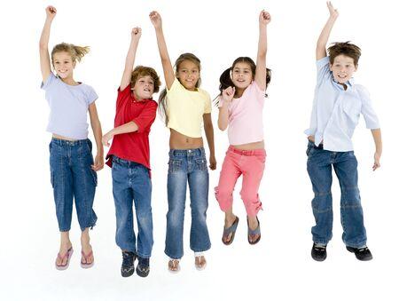 boy jumping: Cinco amigos saltando y sonriendo  Foto de archivo