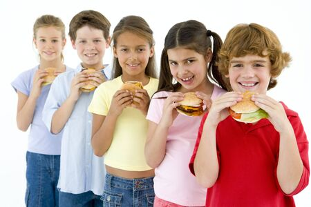 eating out: Row of five young friends eating hamburgers