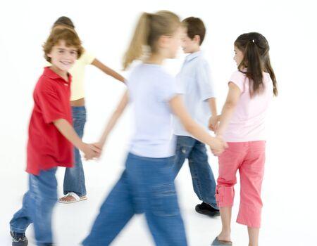 girotondo bambini: Cerchia di cinque giovani amici giocando anello intorno al Rosie sorridente